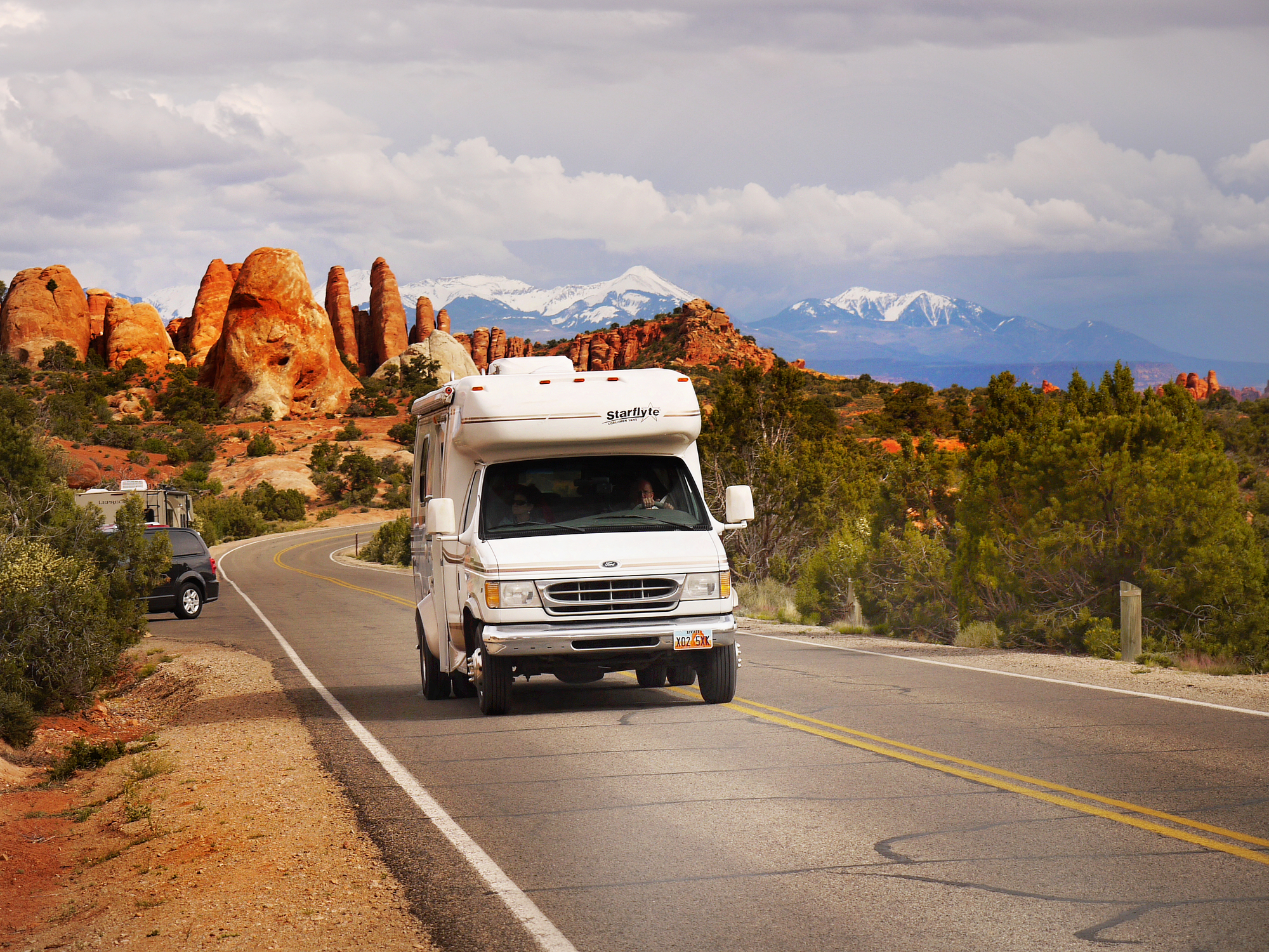 An RV drives past red rocks in Arches National Park, Utah.