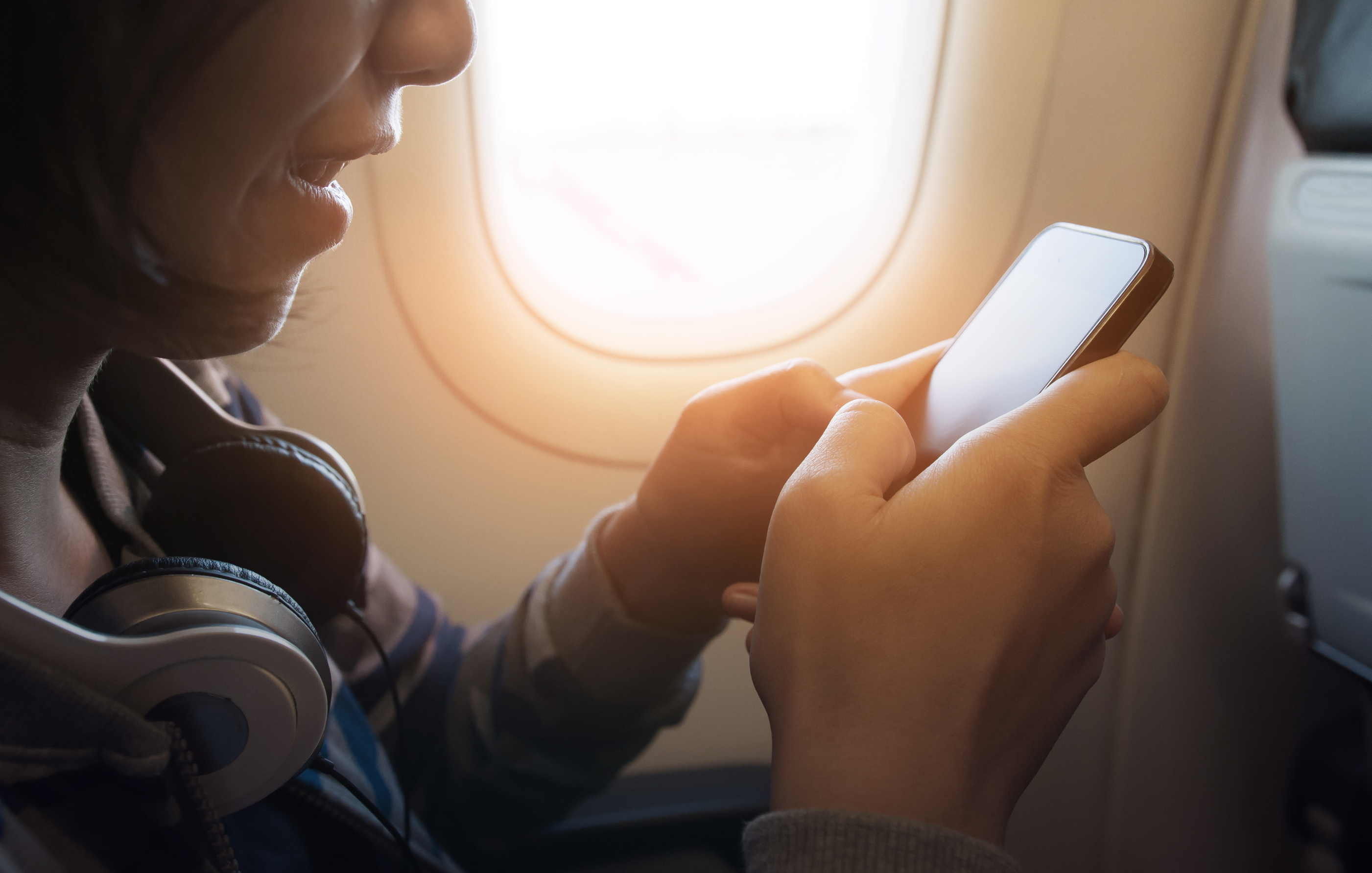 Woman-airplane-window-seat-phone.jpg?mtime=20180710124935#asset:102445