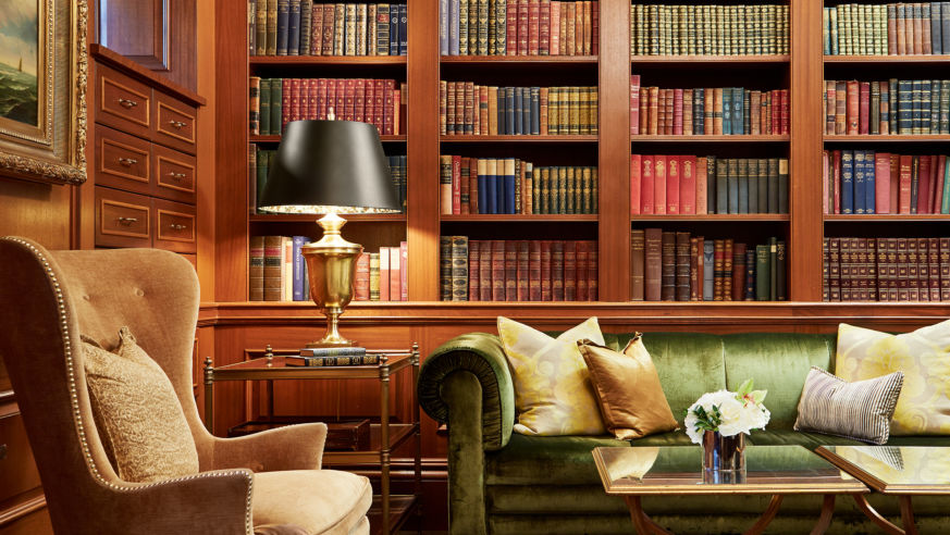 A view of a comfortable chair, sofa, and library shelves at the Jefferson DC Book Room.