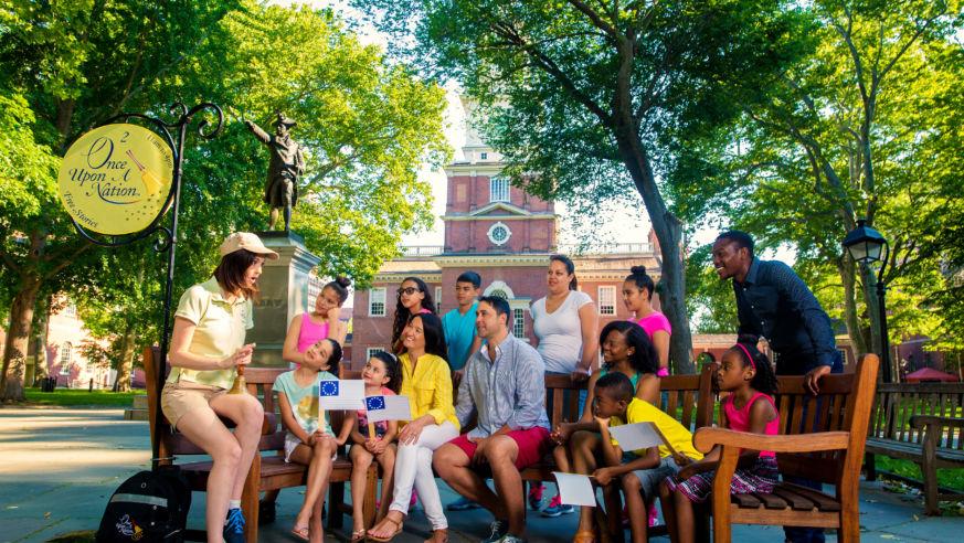 Professional storyteller entertains families on a bench in Philaderlphia