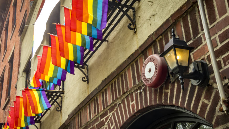 A street view of NYC's Stonewall Inn with rainbow flags.