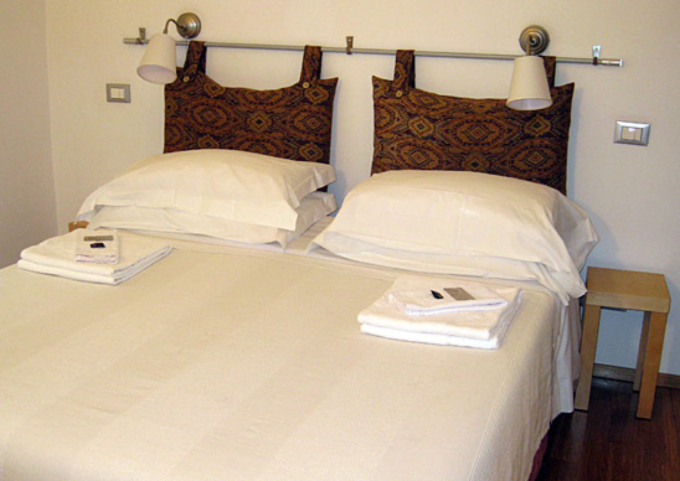 The modern, spare rooms have white linens, some punctuated by batik pillowcases.