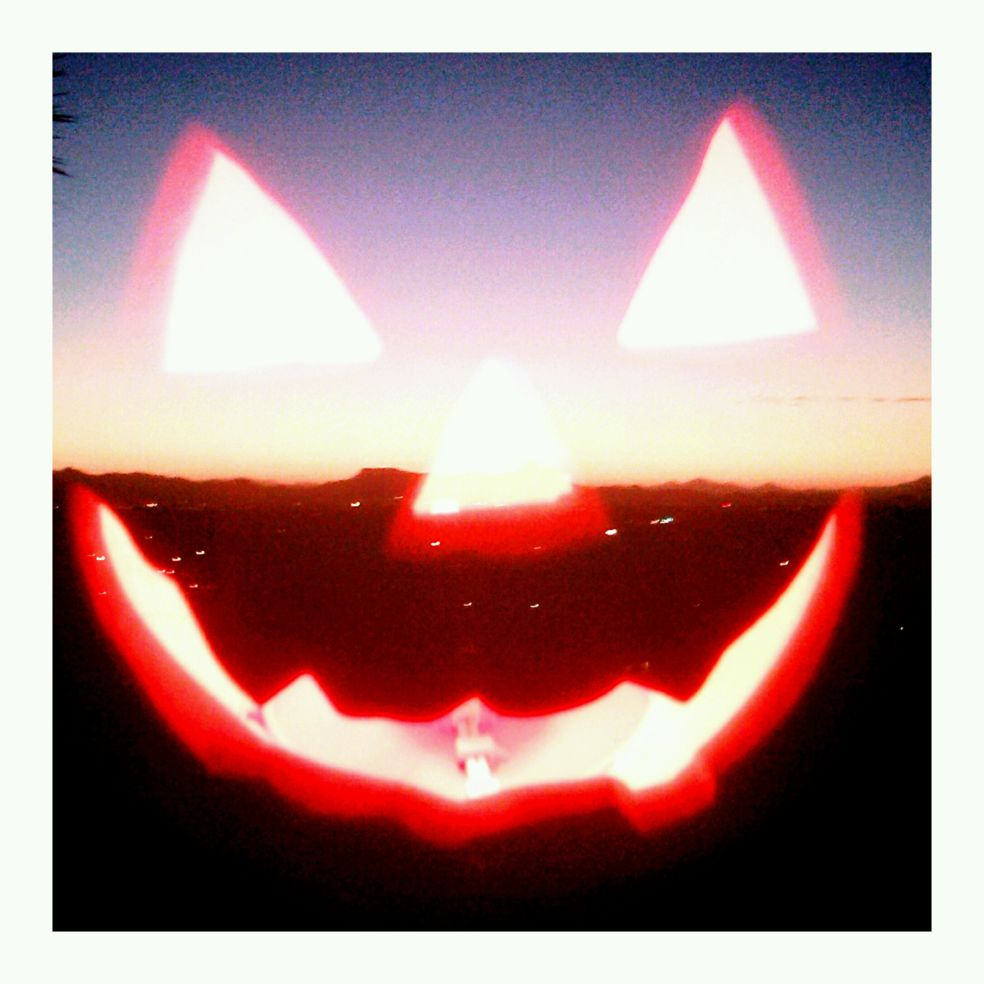 On Halloween night, I shot this juxtaposed photo of a lighted pumpkin with the setting sun on the desert horizon.