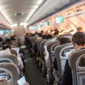 View from the back of a plane of crowded seats.