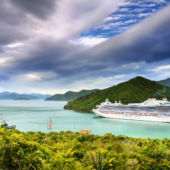 A cruise ship navigates a waterway in beautiful New Zealand mountains