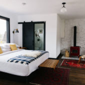 white and black room with queen bed and wood burning stove