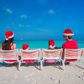 A family of four sits in beach chairs on the sand at the ocean while wearing bright red Santa hats