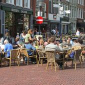A street scene with people at cafe tables in Friesland, Netherlands