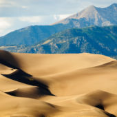 sand dunes with mountain range in backgroud