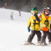 Kids skiing with yellow jackets