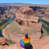 Mikah Meyer wearing a rainbow pride flag as he looks out over Horseshoe Bend