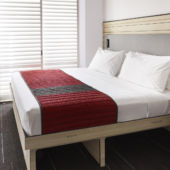 Queen bed with red and white cover in small room