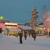 Families in the snow visiting Santa Claus Village in Finnish Lapland