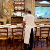A view of an aproned waiter setting a table in Italy