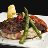 Steak with mashed potatoes and asparagus on a white plate