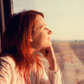 A young woman looks relaxed and satisfied as she looks out a train window while traveling