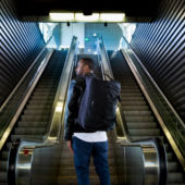 man with backpack at bottom of escalator