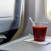 A view of a glass of tomato juice on an airplane tray.