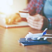 A man books a trip on a computer with his credit card. A toy airplane sits on a passport in the foreground