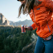 Woman holding can on wine in mountains