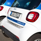 Blue and white SUVs are lined up ready for someone to rent them from the carsharing service Car2Go; Which carsharing service is for you