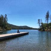 Blue sky dock on lake with person sitting