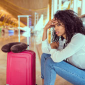 View of a woman sitting at an airport baggage carousel looking frustrated.