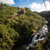 Woman on zipline over river and waterfall