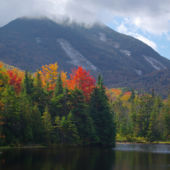 A view of a lake, bright fall colors, and the Adirondack Mountains