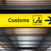 A view of an airport customs sign with an arrow.
