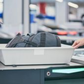 An airport security bin holds a passenger's bag awaiting x-ray