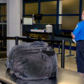 An unattended bag on a TSA security conveyor belt and a TSA agent.