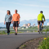 A view of Anchorage's coastal trail with couples walking and cycling