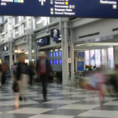 A view of a busy airport terminal with passengers moving quickly.
