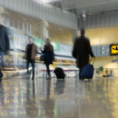 An image of airport passengers moving qjuickly through a terminal