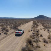 An overhead view of a car on a desert highway.