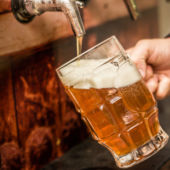 A pint glass being filled with craft beer.