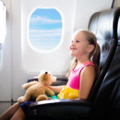 Little girl holding a teddy bear in an airplane window seat