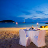 A romantic table with candles on a beach.