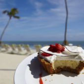 A slice of Key Lime pie on a tropical beach.