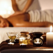 A woman's getting a massage with candles in the foreground