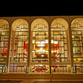 A view of the front windows and chandeliers of the Metropolitan Opera House in New York City.