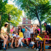 Professional storyteller entertains families on a bench in Philaderlphia
