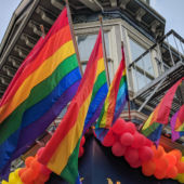 Rainbow pride flags decorate a Victorian-style building in San Francisco's Castro District