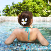 View of a spa pool with a woman relaxing with flowers in her hair.