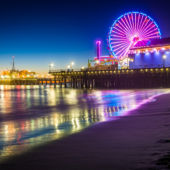 A view from the beach at night of the Santa Monica Pier.