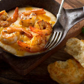 An overhead view of a plate of shrimp and grits with a cheddar biscuit on the side.
