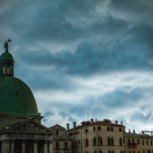 A dome in Venice with storm clouds gathering behind it.