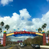 A view of cars entering Walt Disney World, Orlando, with a sign and image of Mickey Mouse