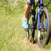 The front tire and pedals of a woman mountain biking on grass
